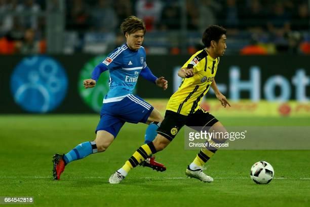 Gotoku Sakai of Hamburg challenges Shinji Kagawa of Dortmund during the Bundesliga match between Borussia Dortmund and Hamburger SV at Signal Iduna...