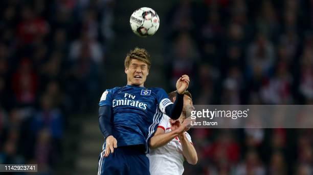 Gotoku Sakai of Hamburg goes up for a header with Simon Terodde of Koeln during the Second Bundesliga match between 1 FC Koeln and Hamburger SV at...
