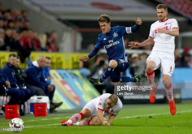 Gotoku Sakai of Hamburg jumps over Johannes Geis of Koeln during the Second Bundesliga match between 1 FC Koeln and Hamburger SV at...