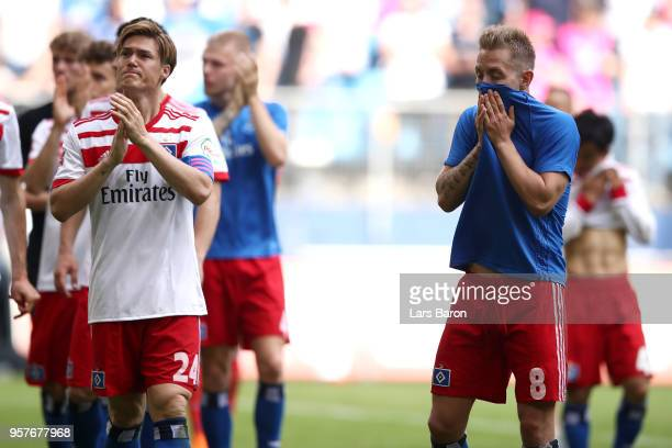 Gotoku Sakai of Hamburger SV and Lewis Holtby of Hamburger SV look dejected as they applaud fans after the Bundesliga match between Hamburger SV and...