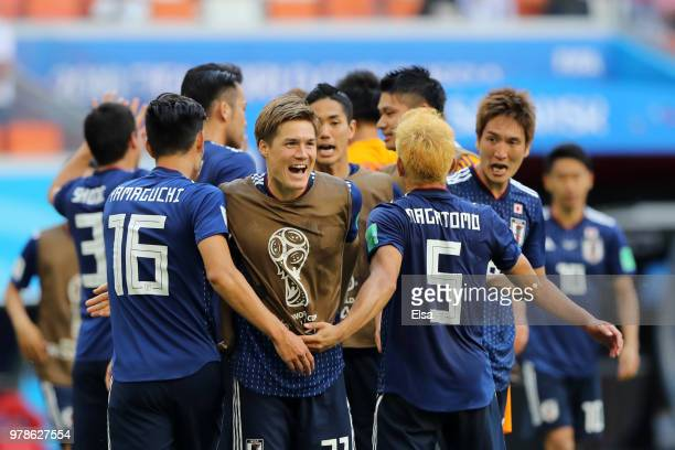 Gotoku Sakai of Japan celebrates with Hotaru Yamaguchi and Yuto Nagatomo of Japan following their sides victory in the 2018 FIFA World Cup Russia...