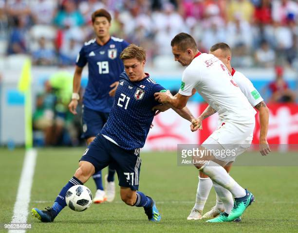Gotoku Sakai of Japan is challenged by Artur Jedrzejczyk of Poland during the 2018 FIFA World Cup Russia group H match between Japan and Poland at...