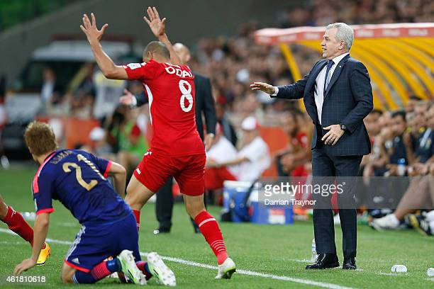 Gotoku Sakai of Japan is taken down by Odai Al Saify of Jordan as coach of Japan Javier Aguirre reacts during the 2015 Asian Cup match between Japan...