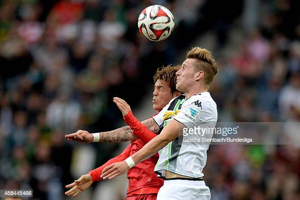 Gotoku Sakai of Stuttgart and Andre Hahn of Moenchengladbach jump for a header during the Bundesliga match between Borussia Moenchengladbach and VfB...