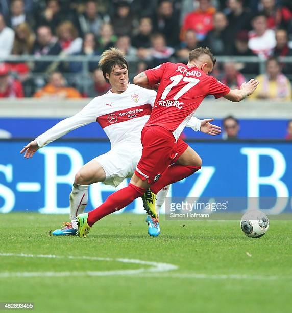 Gotoku Sakai of Stuttgart is challenged by Jonathan Schmid of Freiburg during the Bundesliga match between VfB Stuttgart and SC Freiburg at...