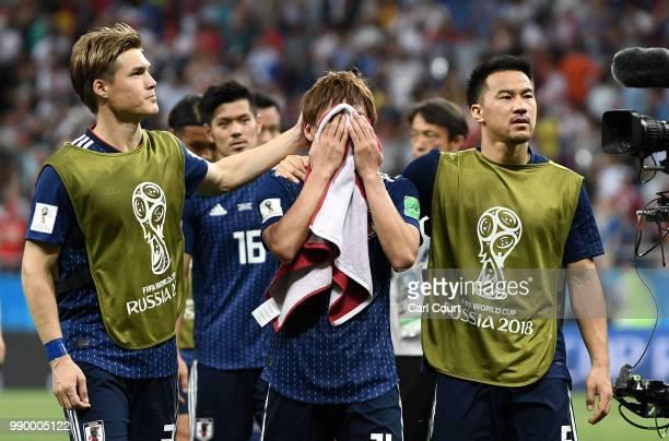 Gotoku Sakai Takashi Inui and Shinji Okazaki of Japan walks off the pitch dejected folowing the 2018 FIFA World Cup Russia Round of 16 match between...
