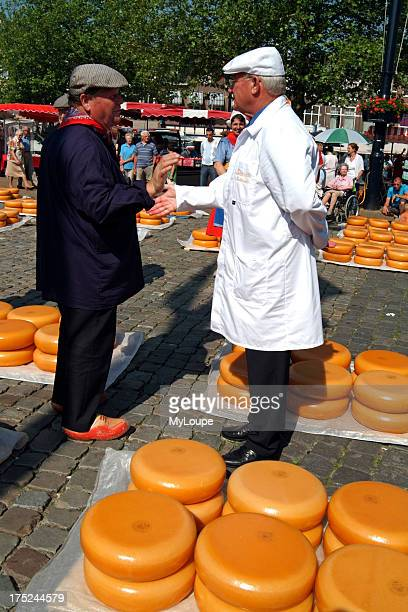 Gouda cheese market Holland Dutch buyer and seller agree a sale of cheese with a slap of hands Gouda town center The Netherlands Europe