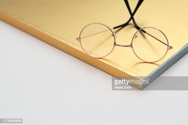 goudkleurig boek met leesbril - boek stock-fotos und bilder