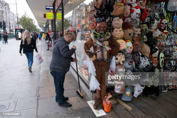 Goulish masks as a mans sweeps up outside a souvenir shop following Halloween as Londoners await the imminent second coronavirus lockdown it's...