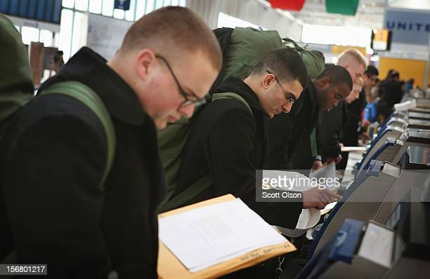 A goup of sailors who recently graduated from boot camp at Naval Station Great Lakes check in for flights at O'Hare International Airport on November...
