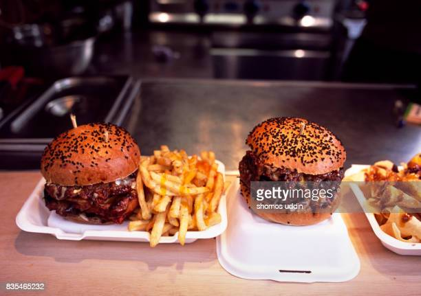 Gourmet burgers and french fries against blurred background