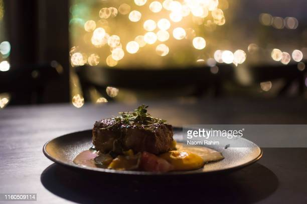 gourmet grilled reindeer entrecote steak, lappish potatoes and sauce, served on a contemporary plate on a dark timber table - garnish stock pictures, royalty-free photos & images