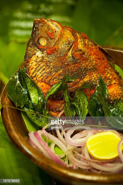 Gourmet Indian fried fish with curry leaves, lemon and onion