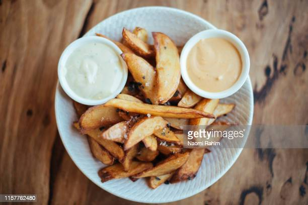 gourmet potato wedges served with black sea salt & aioli in a white bowl, shot directly above - french fries stock pictures, royalty-free photos & images