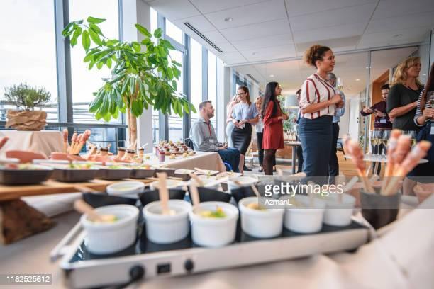 gourmet kleine gerichte und profis genießen büro-party - launch event stock-fotos und bilder