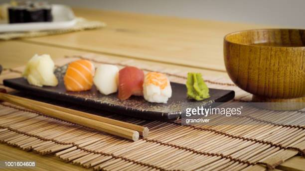 gourmet sushi on a plate with miso soup and chopsticks - sushi restaurant stock photos and pictures