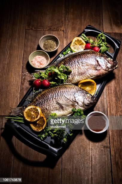 gourmet whole dorado fish on metal skillet pan - dorado fish stock photos and pictures