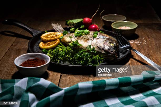 gourmet whole dorado fish on metal skillet pan - dolphin fish stock pictures, royalty-free photos & images
