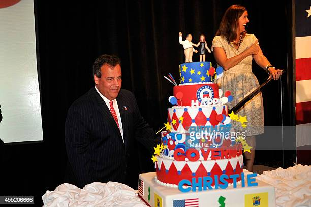 Gov Chris Christie looks at a large birthday cake after he and former Republican presidential contender Mitt Romney addressed an audience during a...
