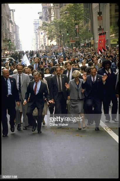 Gov Cuomo VP cand Gerry Ferraro Pres cand Mondale Mayor Ed Koch marching in Columbus Day Parade framed by crowd