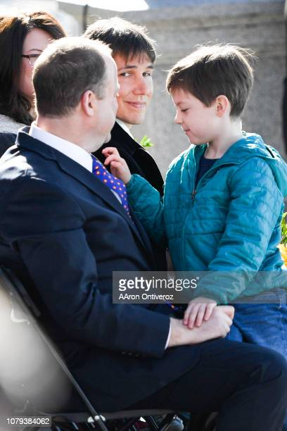 Gov Jared Polis exchanges a look with partner Marlon Reis as their son Caspian plays with Polis' tie during his inauguration at the Colorado State...