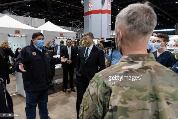 Gov JB Pritzker left and US Army Secretary Ryan McCarthy meet with members of the Illinois National Guard medical professionals and construction...