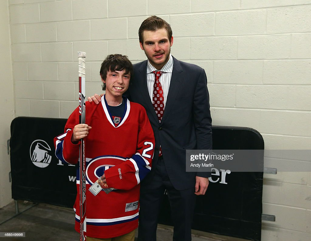 Gov. Livingston HS senior Kyle Kramer, who beat Leukemia, poses for a photo with his favorite hockey player Alex Galchenyuk #27 of the Montreal Canadiens after the conclusion of the game against the New Jersey Devils at the Prudential Center on April 3, 2015 in Newark, New Jersey.
