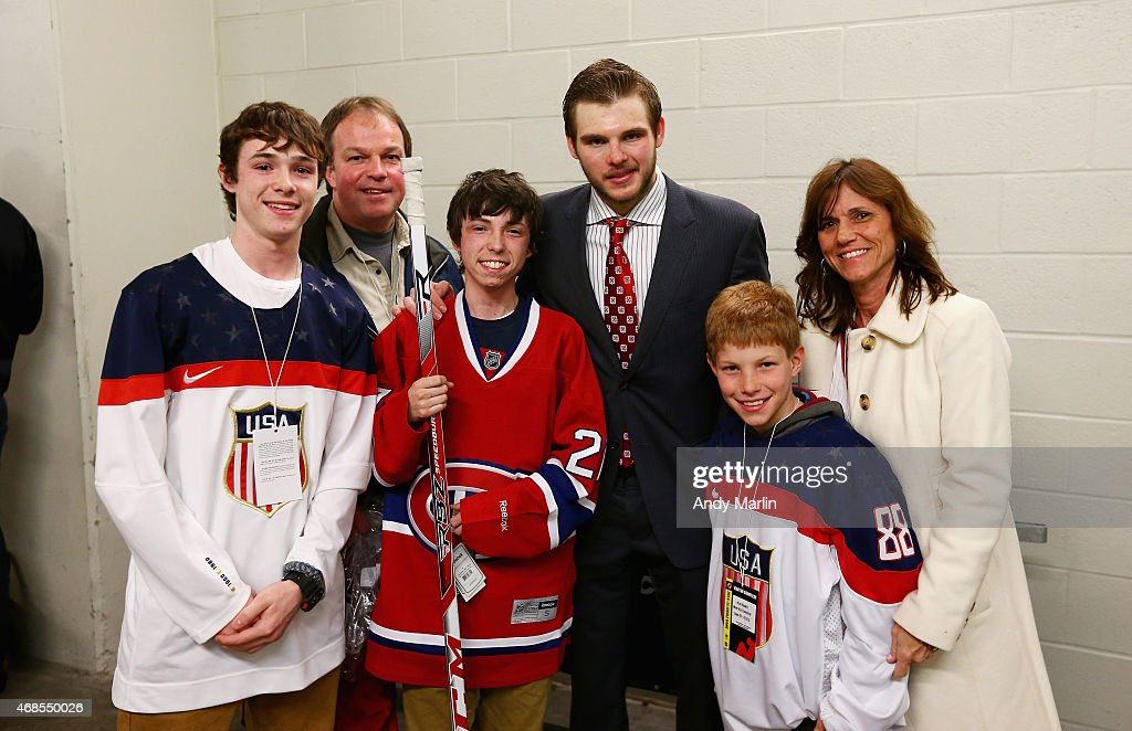 Gov. Livingston HS senior Kyle Kramer (C), who beat Leukemia, poses for a photo with his favorite hockey player Alex Galchenyuk (CR)#27 of the Montreal Canadiens and Kyle's family after the conclusion of the game against the New Jersey Devils at the Prudential Center on April 3, 2015 in Newark, New Jersey.