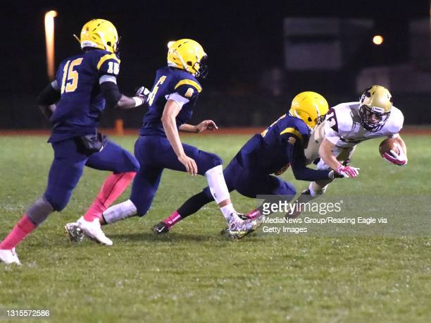 Gov. Mifflin's Bryce Stubler dives for extra yards being pursued by Muhlenberg's Chris Castro , Stefahn Mayo and Shawn Castillo . FOOTBALL - The...