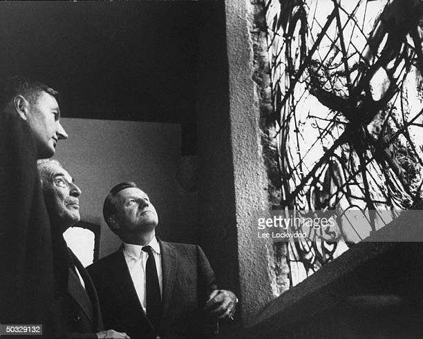Gov Nelson A Rockefeller and David Rockefeller with artist Marc Chagall attending dedication of stained glass window of his design at UN