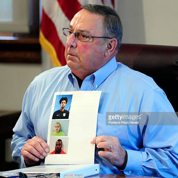 Gov Paul LePage holds up booking mug shots from a threering binder of news releases and articles about drug arrests during a meeting with reporters...