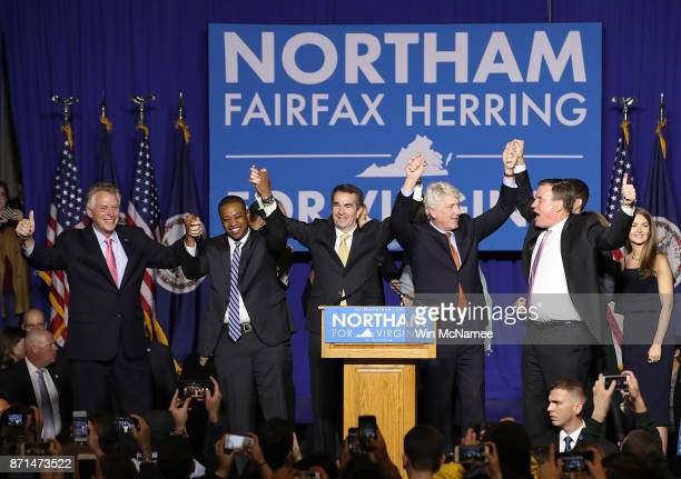 Govelect Ralph Northam links arms with current Gov Terry McAuliffe Lt Govelect Justin Fairfax Attorney Generalelect Mark Herring and US Sen Mark...