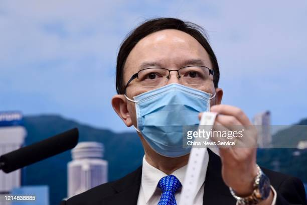 Government Chief Information Officer Victor Lam Waikiu shows a monitoring wristband for people under quarantine during a press conference amid novel...