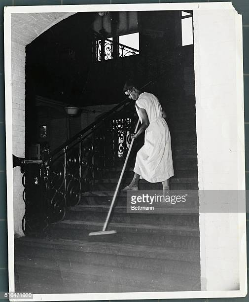 Government cleaning woman Ella Watson brooming down departmental stairs Undated photograph