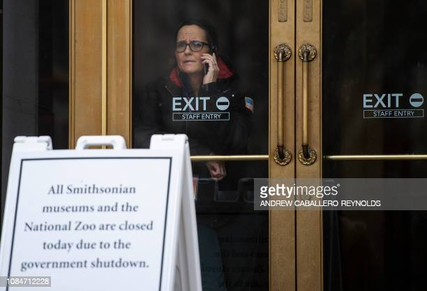 A US government employee talks on the phone as she looks out of a closed Smithsonian museum in Washington DC on January 18 2019 The US federal...