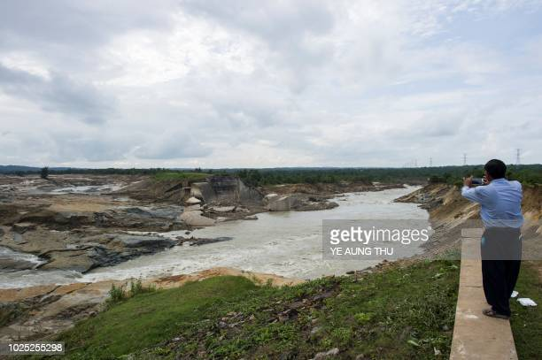 Government engineer view the water draining out from the collapsed spillway of Swar Chaung dam seen at right at Swar township, Bago region on August...