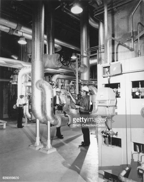 Government inspectors with the Department of Energy check control air ducts on a raw cooling water system in the Tennessee Valley Authority's Browns...