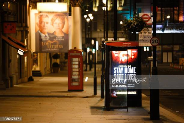 Government messaging telling people to stay at home lights up the digital advertising screen of a bus stop on a near-deserted Haymarket in London,...