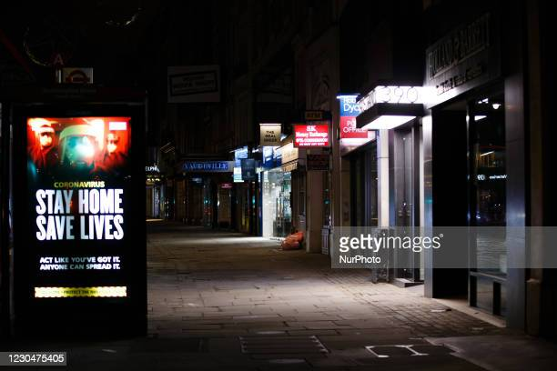 Government messaging telling people to stay at home lights up the digital advertising screen of a bus stop on a near-deserted Strand in London,...