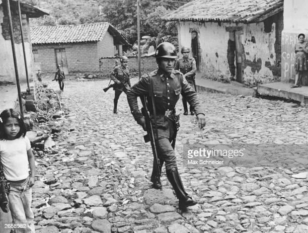 Government militia patrol a village in northern El Salvador during the civil war