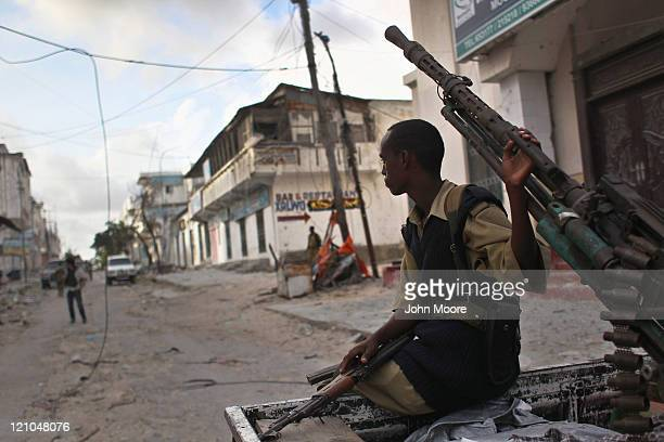 A government militiaman sits on a pickup truckmounted antiaircraft gun in the infamous Bakara market on August 13 2011 in Mogadishu Somalia Islamist...