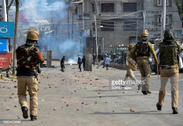 Government officers are seen running after the Kashmiri protesters during the clashes Clashes broke out between militants and government forces in...