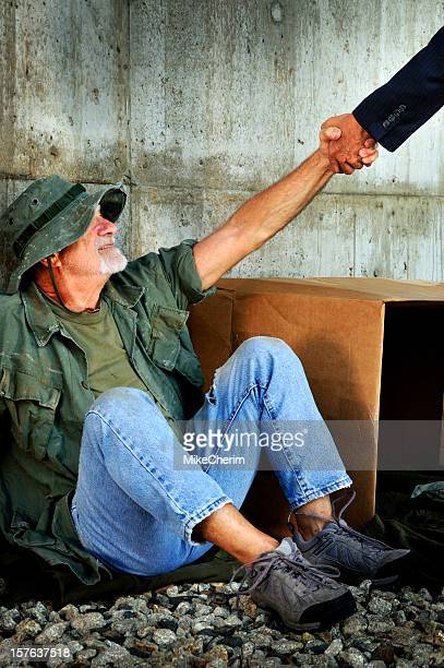 government official giving grateful veteran a hand up - homeless veterans stock photos and pictures