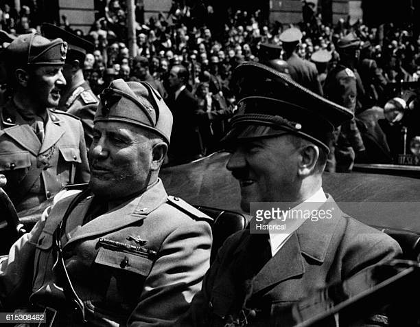 Government officials Adolf Hitler and Benito Mussolini ride past a crowd of spectators in Munich Germany circa June 1940