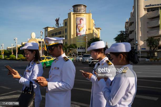 Government officials use smartphones as they gather along the route where Thai King Maha Vajiralongkorn will be traveling to the Royal Palace ahead...