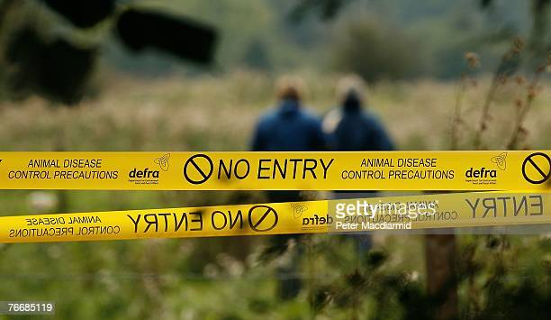 Government officials walk near signs warning of an outbreak of Foot and Mouth disease at farmland on September 12, 2007 near Egham, England. This new...