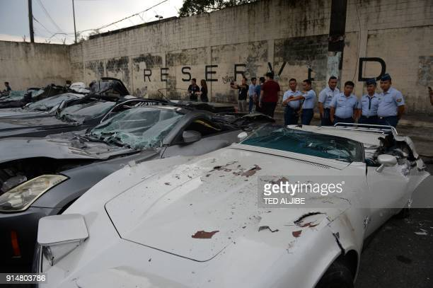 Government personnel view crushed luxury vehicles at a ceremony at the customs yard in Manila on February 6 after they were seized for being smuggled...