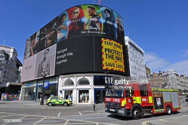 A government sign advising people to Stay Home Protect the NHS Save Lives is displayed on the advertising boards in Piccadilly Circus in the spring...
