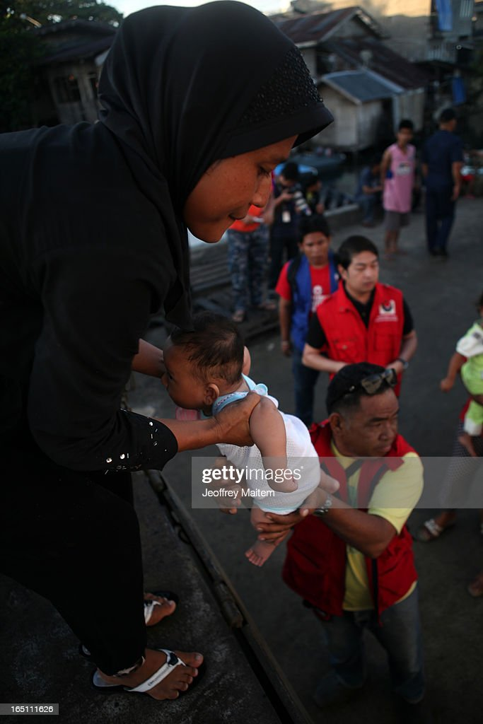 A government social welfare officer lifts a child displaced by continuing armed conflict between the supporters of Philippine Muslim clan Sulu Sultan Jamalul Kiram III and Royal Malaysian Police in Sabah, Malaysia, as they arrive at Bonggao on March 30, 2013 in Bonggao, Tawi-Tawi, Philippines. Following the insurgency in Sabah and the Malaysian government's subsequent crackdown on undocumented Filipinos, over 4000 people, mostly Filipino Muslims, have begun evacuating to the southern provinces of Basilan, Sulu, and Tawi-Tawi in the Philippines, with numbers expected to reach more than 100,000.