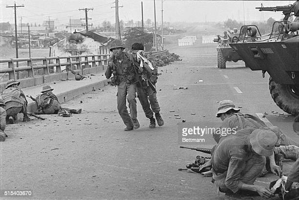 A government soldier helps his wounded buddy on the Newport Bridge during fighting with Communist insurgents